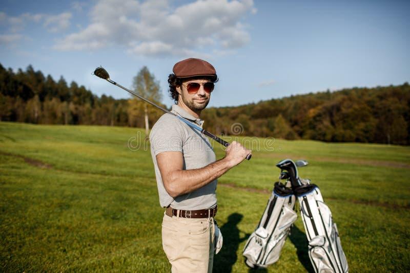 Полнометражный взгляд человека в крышке держа гольф-клуб и ударяя bal стоковые изображения