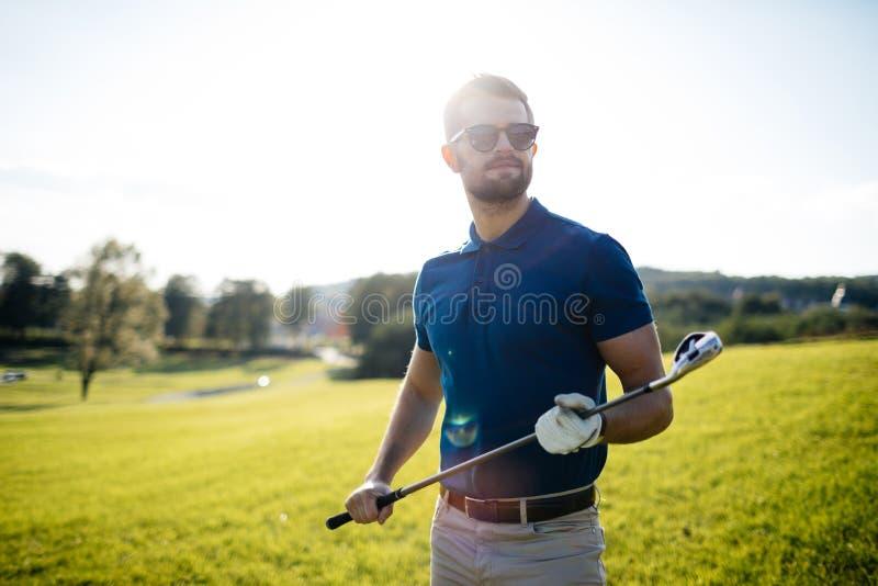 Полнометражный взгляд человека в крышке держа гольф-клуб и ударяя bal стоковые изображения rf