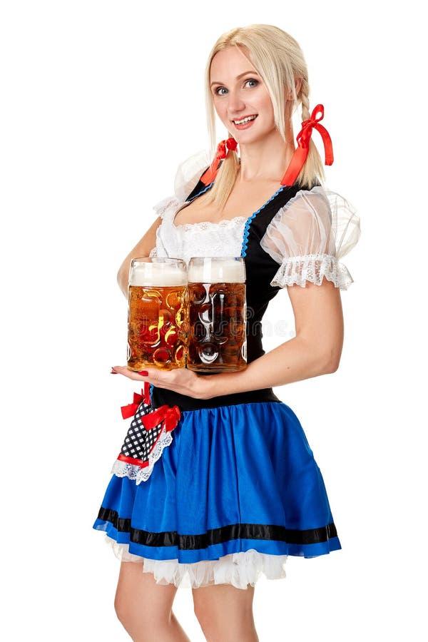 Полнометражный портрет белокурой женщины при традиционный костюм держа стекла пива изолированный на белой предпосылке стоковое изображение
