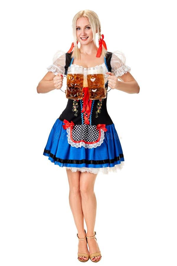 Полнометражный портрет белокурой женщины при традиционный костюм держа стекла пива изолированный на белой предпосылке стоковые изображения rf
