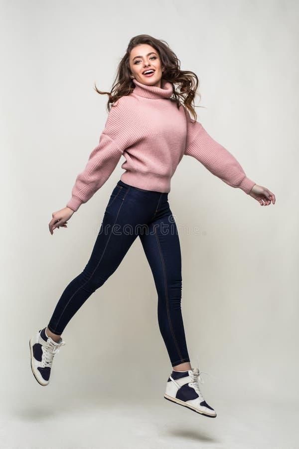 Полнометражный портрет вскользь молодой женщины скача и смотря камера изолированная над белой предпосылкой стоковое фото