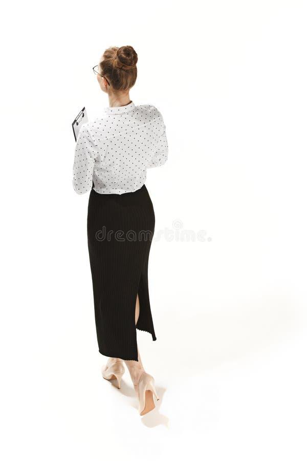 Полнометражный портрет задней части учительницы держа папку изолированный против белой предпосылки стоковое изображение rf