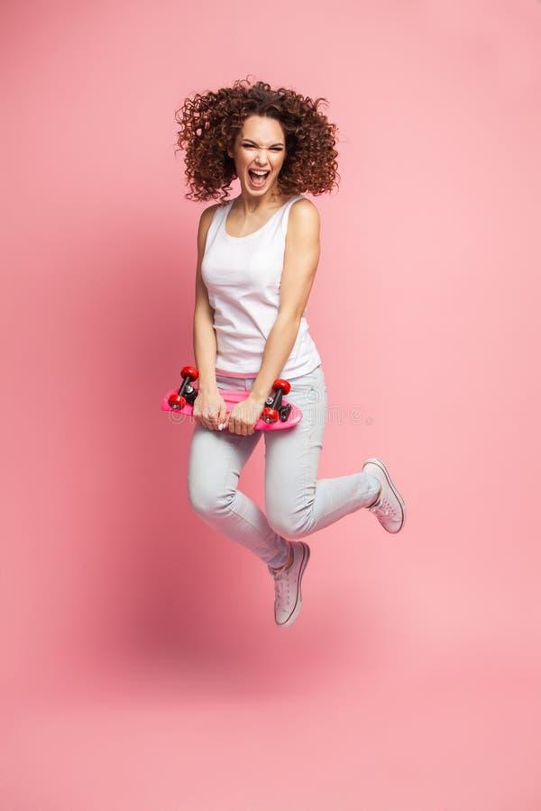 Полнометражный портрет красивой счастливой женщины в лете одевает представлять и смотреть отсутствующим пока скачущ и держащ стоковая фотография rf