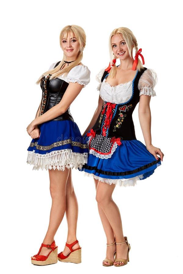 Полнометражный портрет 2 красивых женщин в традиционном костюме изолированном на белизне oktoberfest стоковая фотография