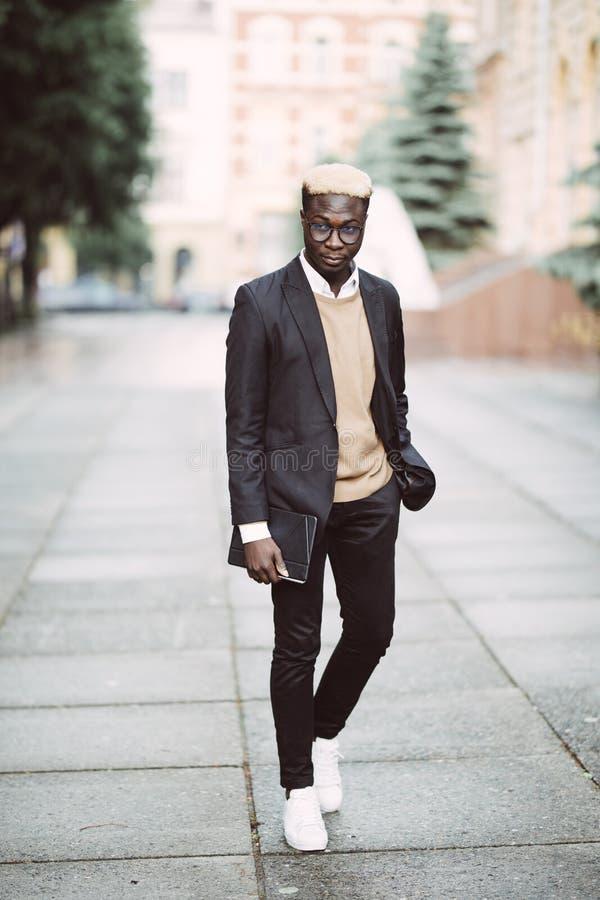Полнометражный портрет молодого африканского бизнесмена идя в улицу города стоковые фото