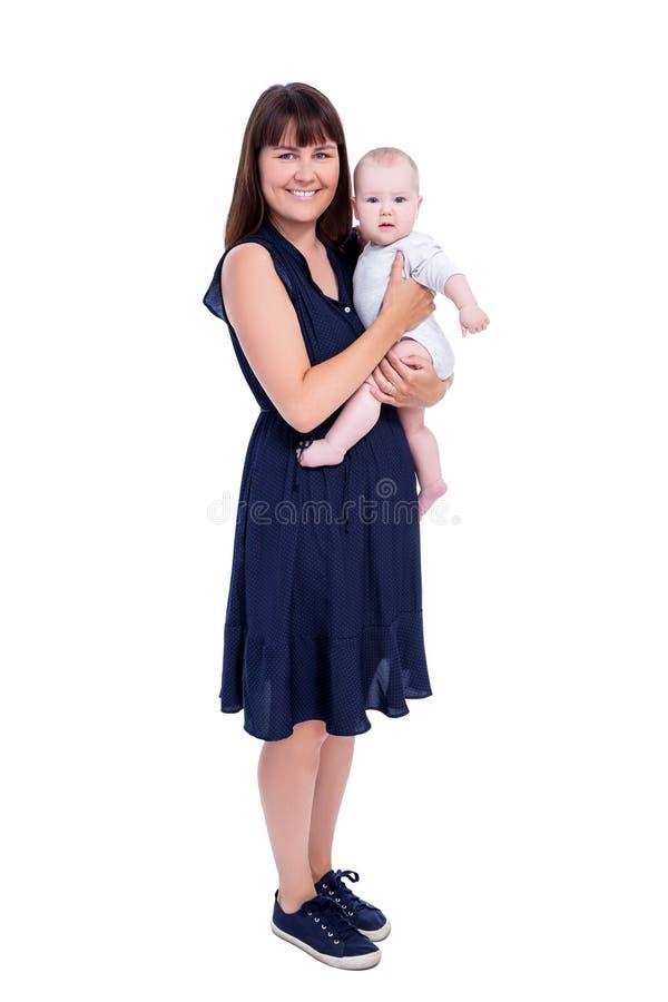 Полнометражный портрет молодой матери с маленьким младенцем изолировал o стоковое фото