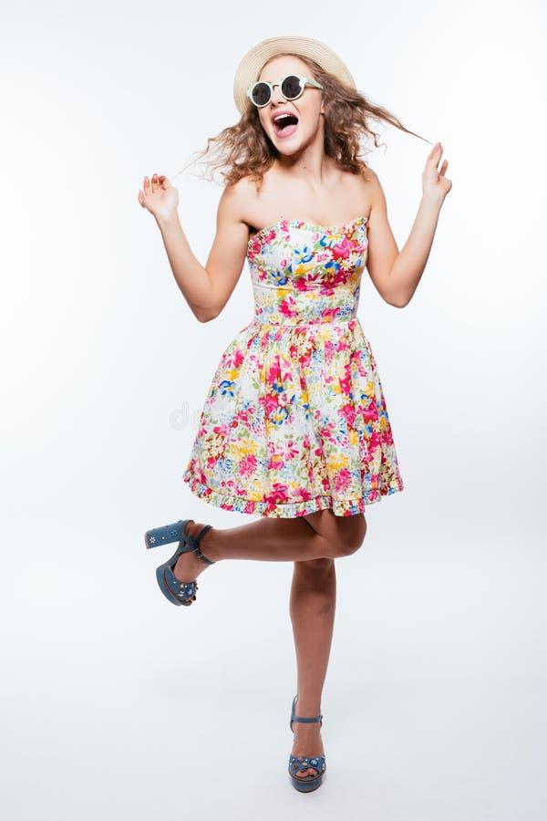 Полнометражный портрет представлять солнечных очков шляпы и платья довольно курчавой с волосами женщины нося изолированный над бе стоковая фотография