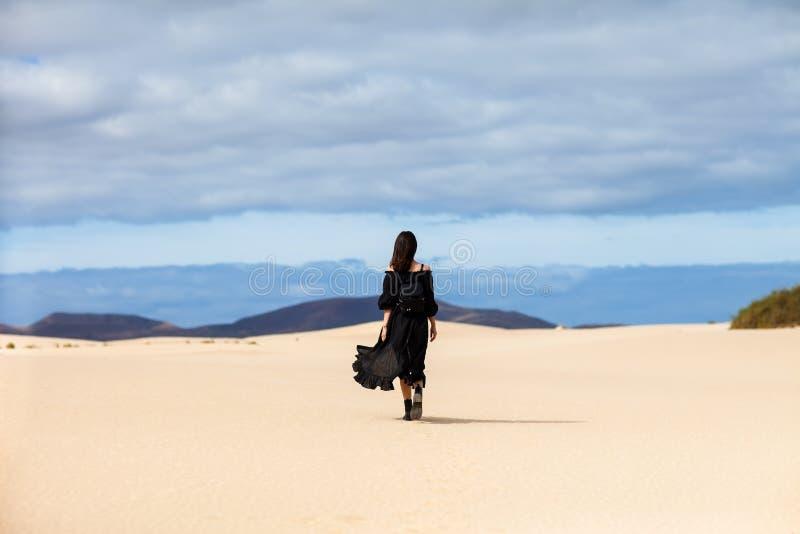 Полнометражный портрет сиротливой женщины идет прочь в пустыню дальше может стоковое фото rf