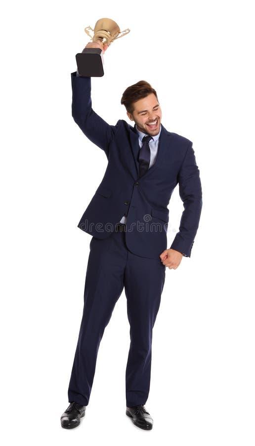 Полнометражный портрет счастливого молодого бизнесмена с чашкой трофея золота на белизне стоковое фото