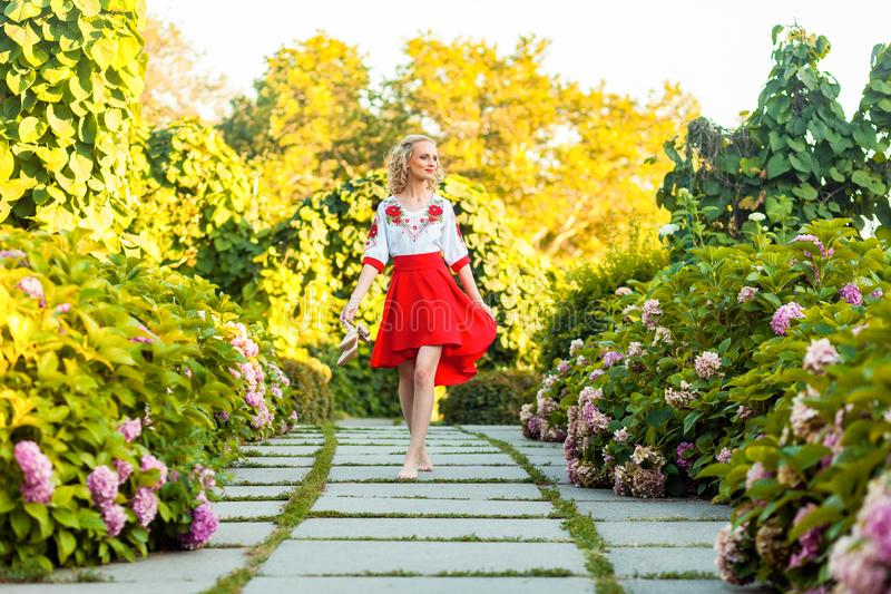 Полнометражный портрет счастливой босоногой привлекательной женщины в стильном красном белом платье держа ботинки и идя на путь п стоковое фото