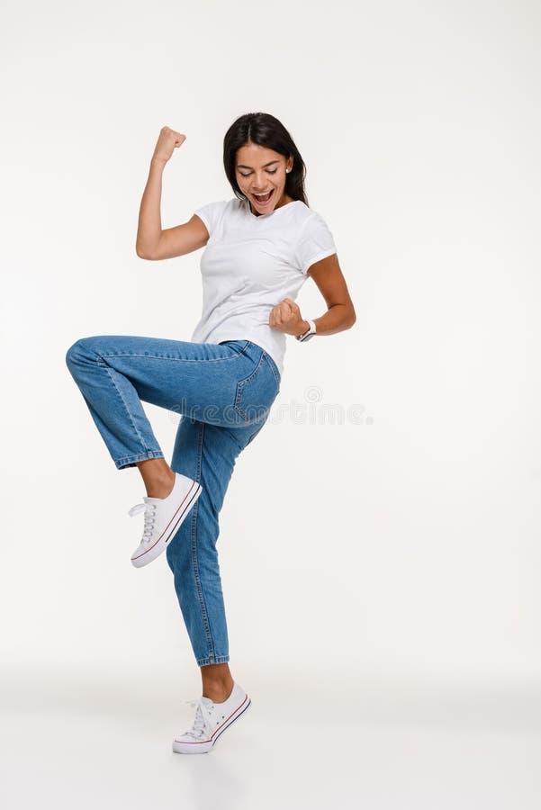 Полнометражный портрет счастливой молодой женщины празднуя успех стоковое фото rf