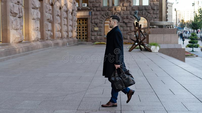Полнометражный портрет уверенного молодого бизнесмена идя в город с сумкой стоковые фото