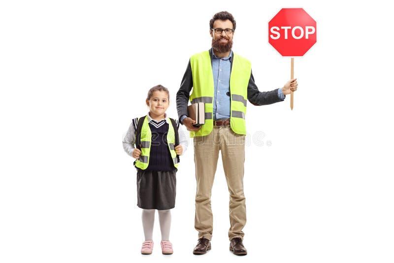 Полнометражный портрет школьницы с жилетом безопасности и учителем держа знак стопа стоковое фото rf