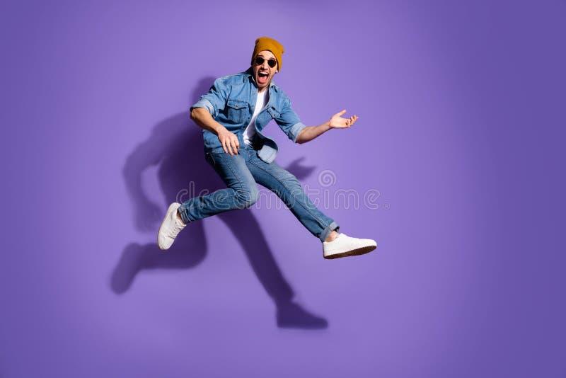 полноразмерное фото взволнованного гитариста, прыгающего под бегом быстро играющего на гитаре в джинсах denim trendy стоковая фотография