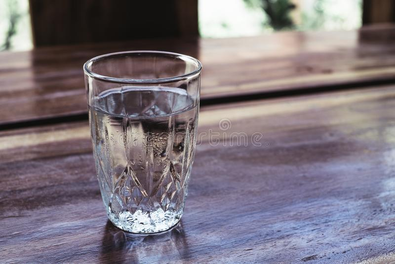 Полностью чистое выпивая стекло воды на деревянном столе стоковые изображения