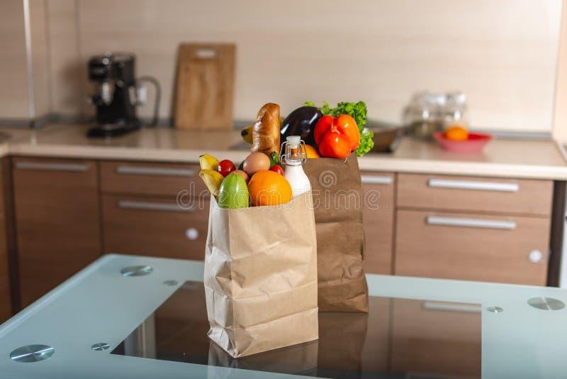 Полные бумажные мешки с едой на таблице на предпосылке кухни Здоровые  стоковые фото