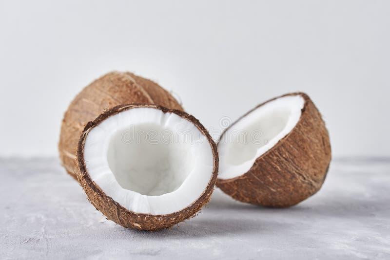 Полный кокос и треснутая половина на белой предпосылке, конец вверх стоковое изображение rf