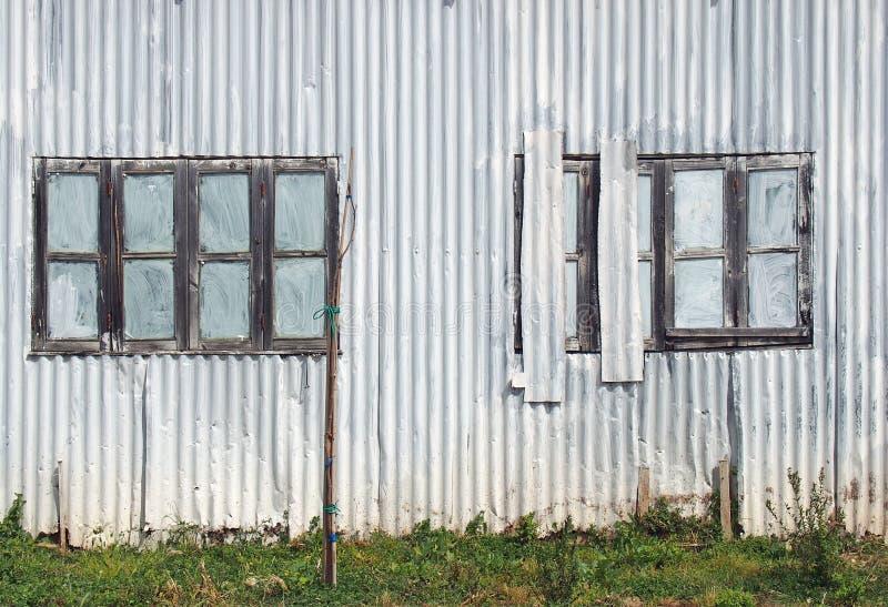 полный конец рамки вверх затрапезного старого разрушанного здания волнистого железа с с закрытым покрашенным над залатанными окна стоковое фото