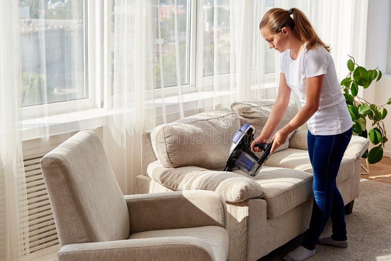Полный портрет тела молодой женщины в белой рубашке и джинсах очищая софу с пылесосом в живущей комнате, космосе экземпляра house стоковое фото