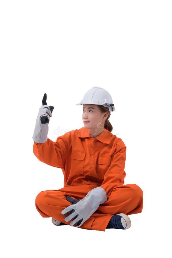 Полный портрет тела работника женщины в комбинезоне механика сидит палец вверх по изолированный на белой предпосылке стоковое изображение