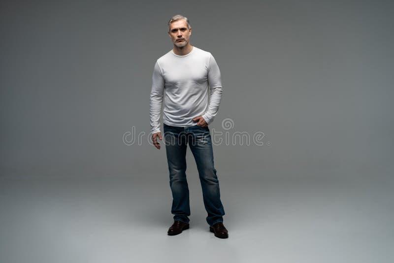 Полный портрет тела расслабленного зрелого положения человека над серой предпосылкой стоковое фото rf
