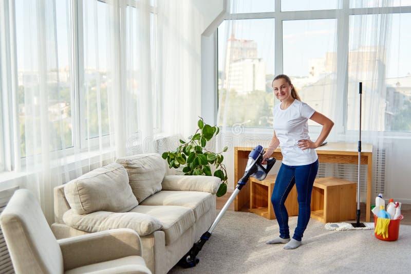 Полный портрет тела усмехаясь женщины в белой рубашке и джинсах очищая ковер с пылесосом в живущей комнате, космосе экземпляра стоковые изображения rf