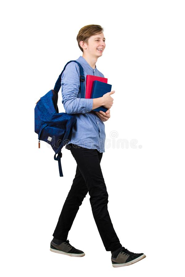 Полный портрет уверенного ученика, идущего в школу, с двумя книгами и рюкзаком Веселый подросток стоковая фотография