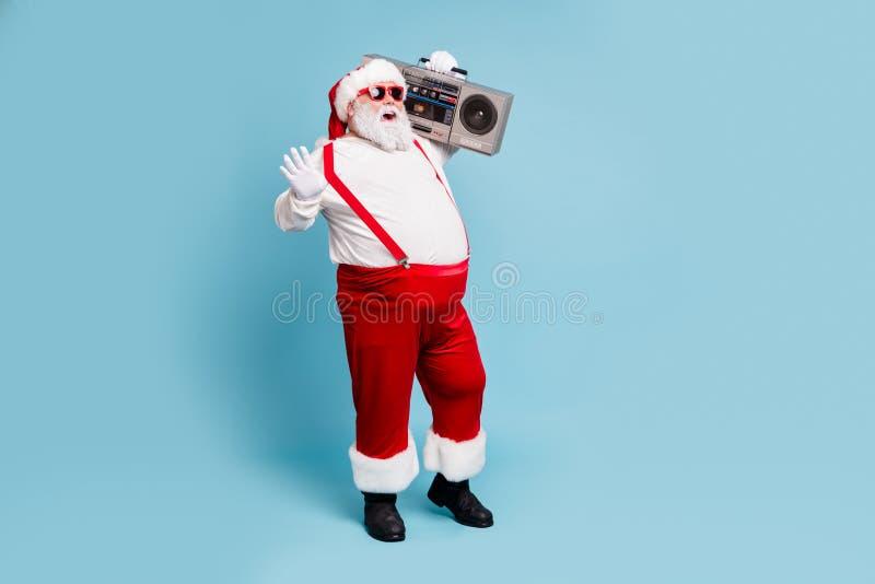 полный размер тела вид на его красивый бородатый бодрствующий радостный счастливый санта с ленточным кассетным плеером стоковые фото