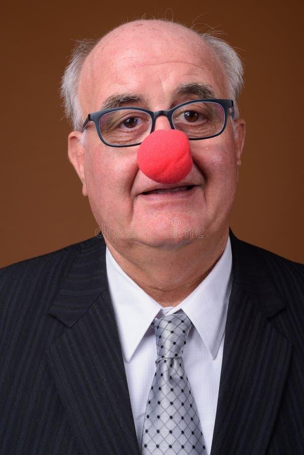 Полный старший бизнесмен нося красный нос клоуна стоковые изображения rf