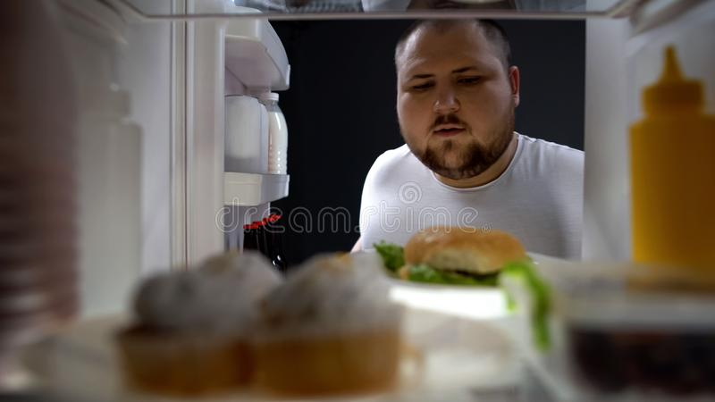 Полный холодильник отверстия молодого человека вечером для того чтобы принять большой бургер, калории стоковое изображение