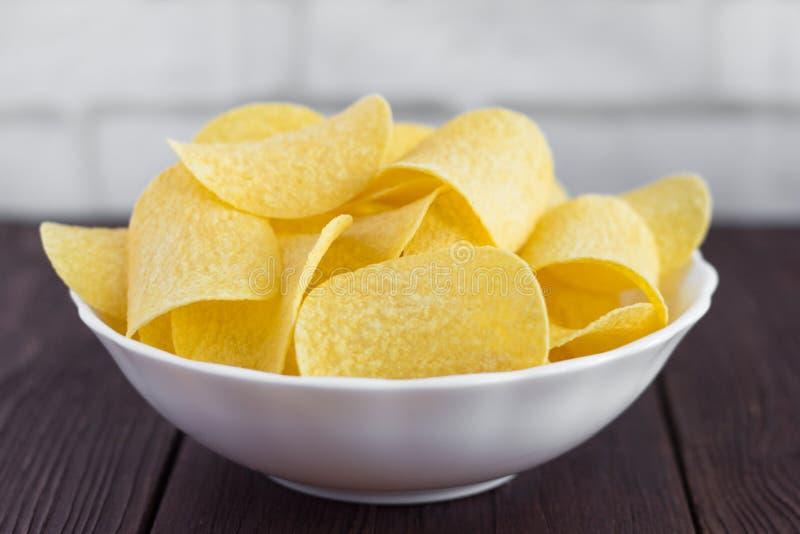 Полный шар очень вкусных картофельных чипсов на деревянном столе, конца-вверх стоковые фотографии rf