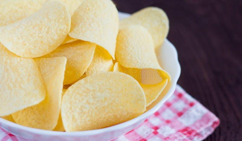 Полный шар очень вкусных картофельных чипсов на деревянном столе, конца-вверх стоковое фото