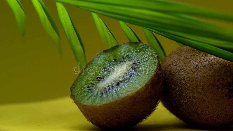 Половина кивиа под тропическими лист, экзотическим сочным плодоовощ, здравоохранением, закуской витамина стоковая фотография