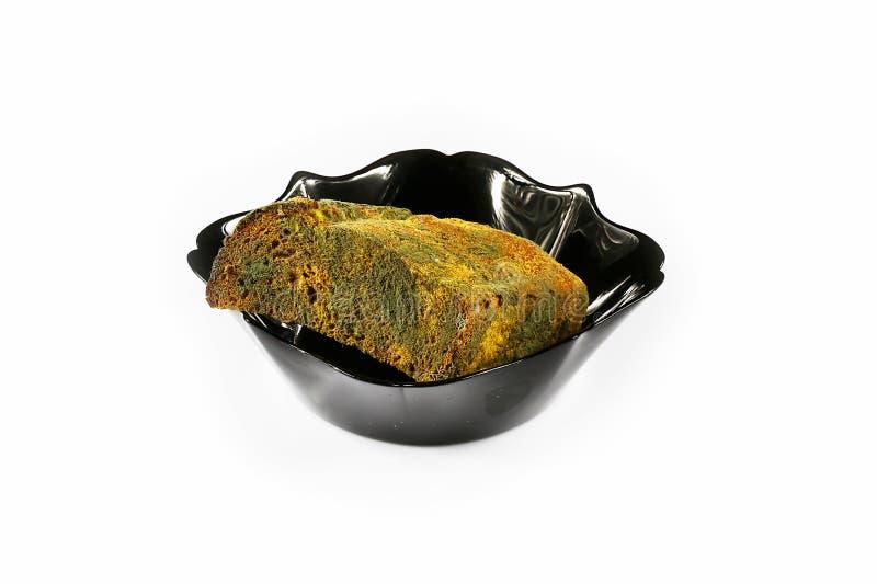 Половина хлебца mouldy хлеба рож в черной плите изолированной на белой предпосылке, концепции несъедобных продуктов, крупном план стоковая фотография rf