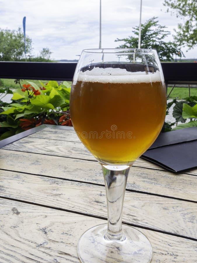 Половинное стекло пива на красивой деревянной старой таблице на веранде ресторана стоковая фотография rf