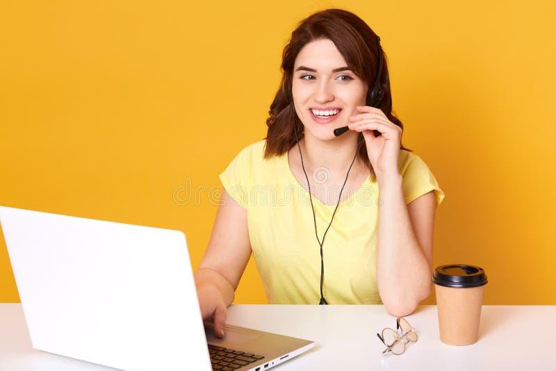 Половинное фото lengh оператора женщины сидя на столе офиса, смотря в сторону, касающий шлемофон, над желтой предпосылкой, стоковые изображения rf