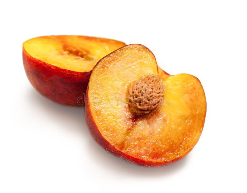 Половинный зрелый персик приносить при камень изолированный на белой предпосылке стоковые изображения rf