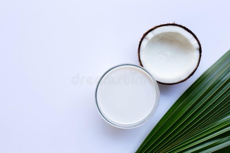 Половинный кокос со стеклянным шаром молока кокоса на белизне стоковое фото rf