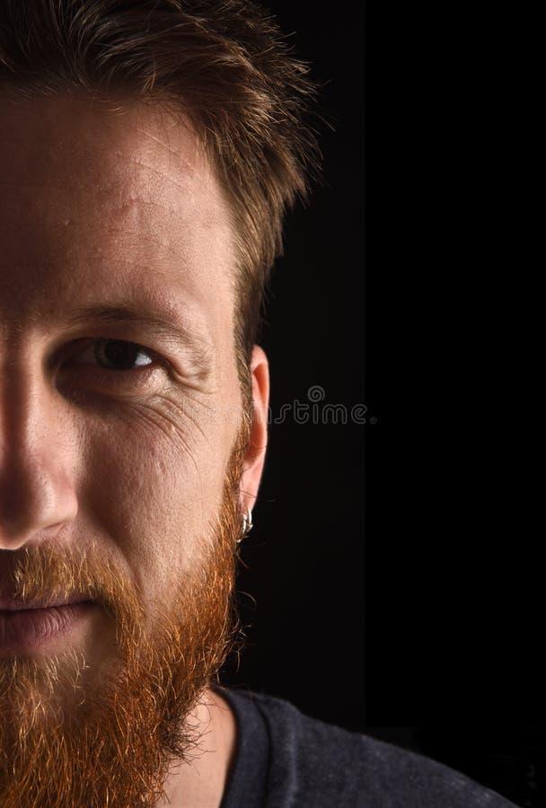 Половинный портрет конца человека вверх по смотреть камеру на черной предпосылке стоковая фотография rf
