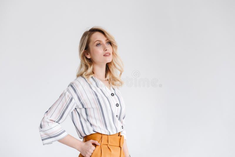 Половинный портрет поворота молодой славной женщины нося случайные одежды смотря в сторону на copyspace с рукой в ее кармане стоковая фотография