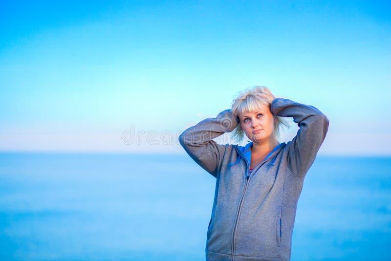 Половинный портрет тела молодой женщины наслаждаясь ветерком на пляже стоковое фото