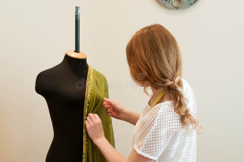 Положение белошвейки и выправлять зеленую ткань на манекене в шить студии стоковое фото