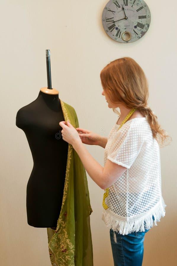Положение белошвейки около манекена и выправлять зеленую ткань стоковые изображения rf