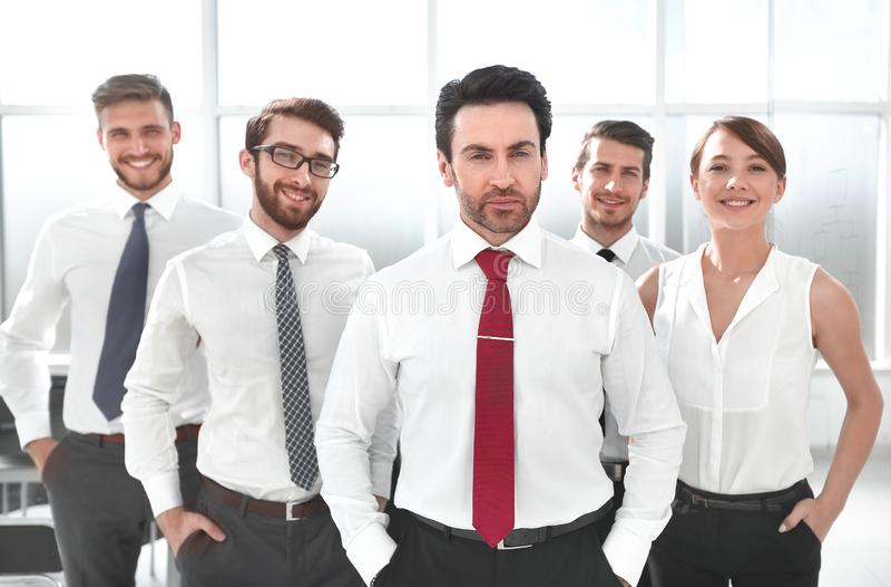Положение бизнесмена перед его командой дела стоковое изображение