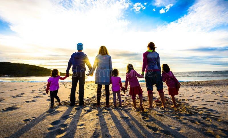 Положение группы семьи и друзей на пляже держа руки стоковое фото