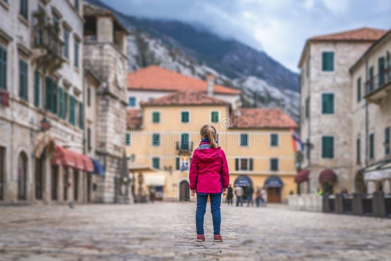 Положение девушки на главной площади городка Kotor старой стоковое изображение rf