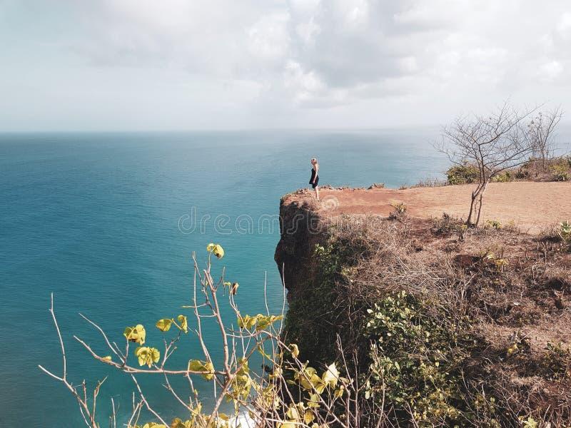 Положение девушки туристское на скале стоковые фото