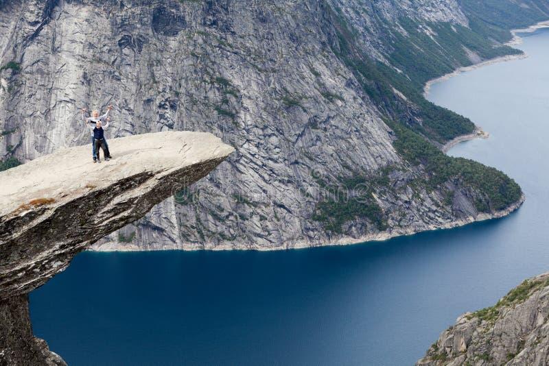 Положение деда и внука на руках горной породы и развевать Trolltunga Выступающая скала в Odda, графстве Hordaland, стоковое изображение rf