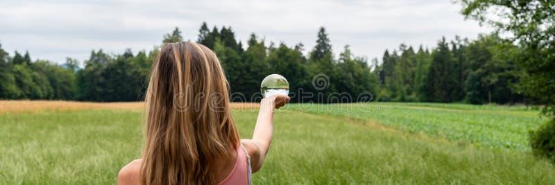 Положение женщины в природе держа хрустальный шар стоковое изображение rf