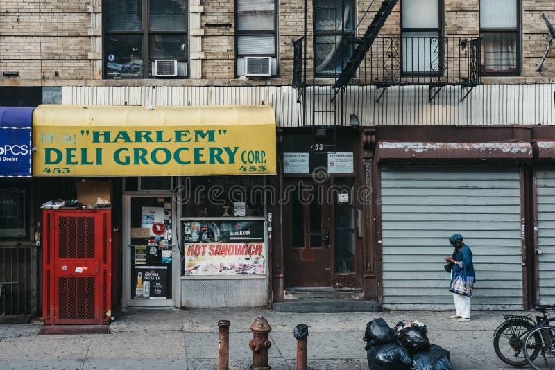 Положение женщины на улице рядом с гастроном в Гарлеме, NYC стоковые фото